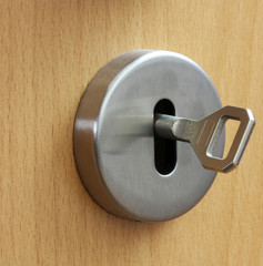Closeup of an  keyhole with key on a wooden  door