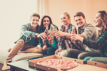Multi-ethnic friends with pizza and bottles of drinks