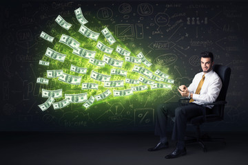 Businessman sitting in chair holding tablet with dollar bills co