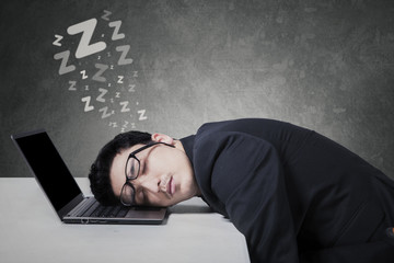 Male businessperson sleeping on laptop