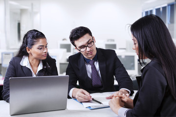 Male manager pointing a document in meeting