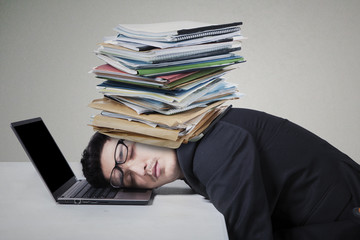 Male worker sleeping on laptop with paperwork