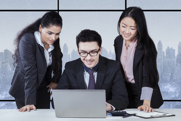 Male worker using laptop with two partners