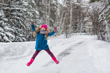 Little girl high jumps winter forest