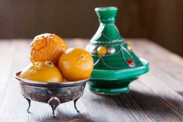 Moroccan pickled lemons in a metal bowl and tagine