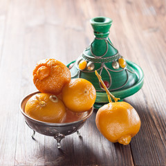 Moroccan pickled lemons and tagine on a wooden background