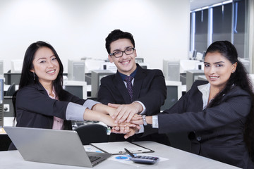 Multi ethnic business team joining their arms
