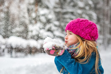 Cute little girl blows snow from hands