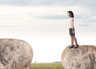 Businesswoman on rock mountain