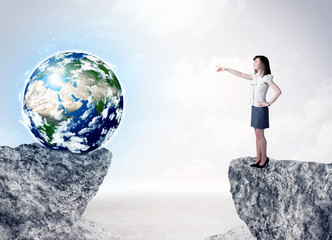 Businesswoman on rock mountain with a globe