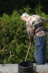 senior man gardener with gloves shoveling his garden