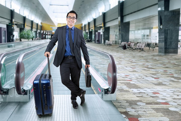 Smiling businessman with luggage in airport hall