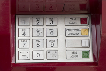 Metallic pinpad ATM on a red background