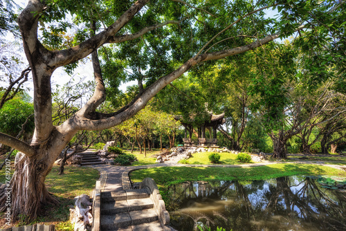 Chinese classical garden with pavilions and pond - 76192107