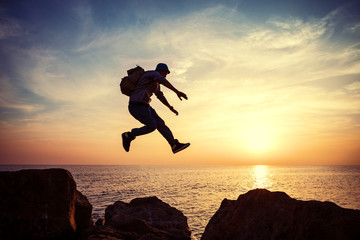 brave man with backpack jumping over rocks near ocean in sunset