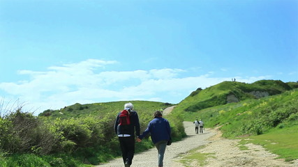 Elderly couple walks up the hill holding hands