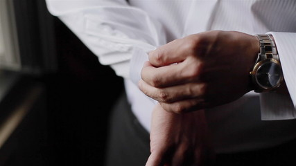 Man puts cufflinks on sleeves of white shirt. Close-up