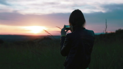 Young woman takes pictures of sunset with smartphone