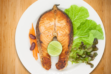 Salmon steak with lemon, bean, carrot, and lettuce on wood table