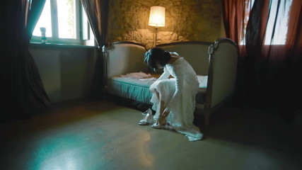 Bride puts on her shoes in a beautiful antique interior
