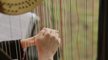 Hands of harpist playing harp. Close-up