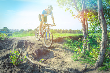 Athlete on a mountain bike rides along the dirt road