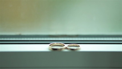 Focus shift from a street outside the window to wedding rings
