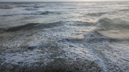 Reverse clip of slow motion waves breaking a shore