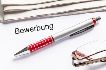Bewerbung mit Zeitung Stift und Brille