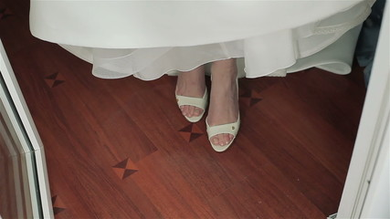 Bride in wedding shoes steps on the floor. Close-up