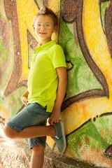 Young kid standing near graffiti wall