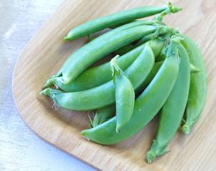 Fresh garden pea isolate on wooden tray