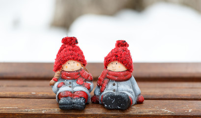 two dolls sitting on bench at winter day