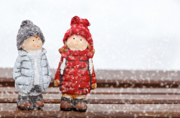 two dolls stand on desk at winter day, snowing