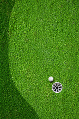 The ball at the hole on the golf course