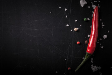 Red hot chilli pepper with sea salt and colored pepper on black