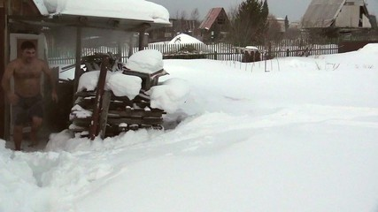 Russian sauna. Young man bathing in the snow