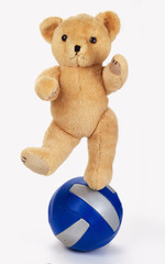 Teddy Bear balancing on ball, isolated on white