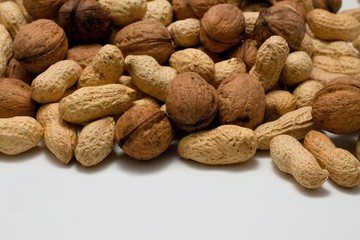 Heap of walnuts and peanuts on white board