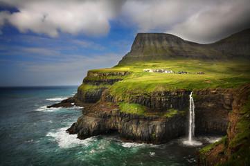 Gasadalur village in Faroe Islands. Cliffs and waterfall.