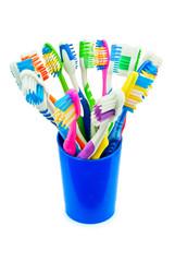 Разноцветные зубные щетки в синем стакане