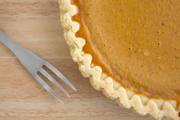 Pumpkin pie with fork on a wood table