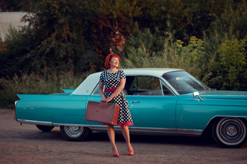 Retro hitchhiker girl with suitcase standing near blue Cadillac