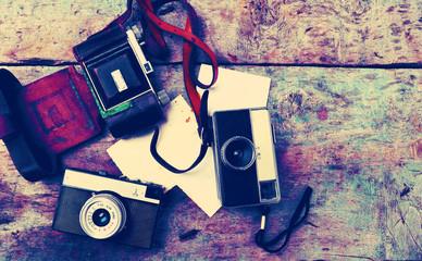 Old retro cameras on vintage wooden background