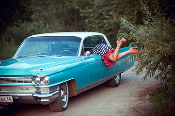 Retro girl getting into blue Cadillac through the window