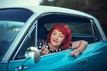 Retro girl holding red lipstick and sitting in blue Cadillac