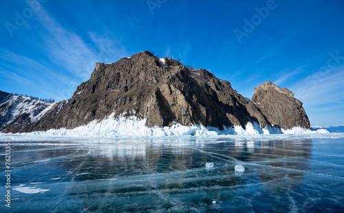 Leinwanddruck Bild Lake Baikal in winter. Smooth ice around rocky island