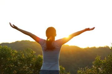 woman open arms sunrise mountain peak