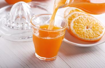 succo di arancia versato nel bicchiere di vetro
