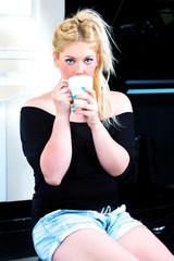 Blonde Frau trinkt Kaffe in der Küche
